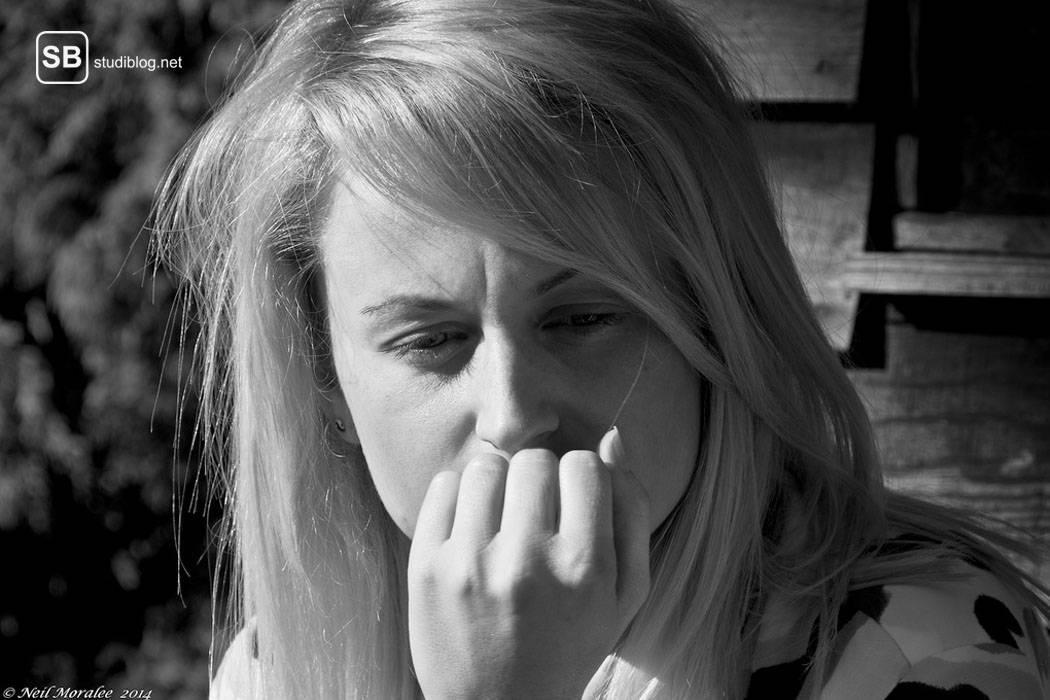 Blonde Frau stützt ihren Kopf auf der geschlossenen Hand ab und schaut Gedanken versunken Richtung Boden - geteilte Aufmerksamkeit.