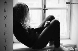 Eine Frau sitzt mit angelehntem Rücken auf einer Fensterbank mit nach vorn geneigtem Kopf, so dass die Haare ihr Gesicht verdecken - sie kämpft mit Depressionen, besser gesagt mit Saddy.