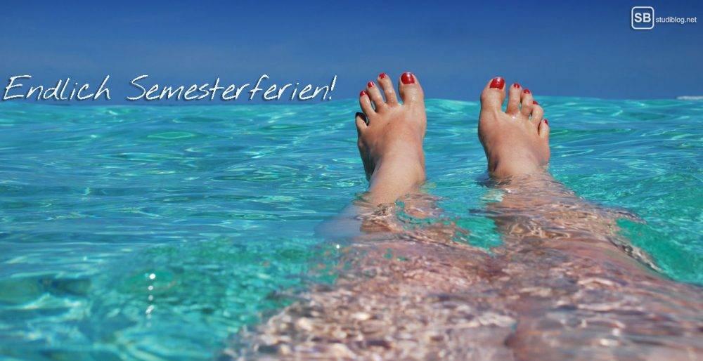 Endlich Semesterferien! - Die rot lackierten Füße einer Frau schauen aus dem Meer