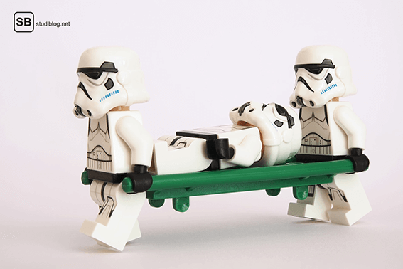 2 Lego-Sturmtruppler von Stars Wars tragen einen weiteren Sturmtruppler mit einer grünen Liege nach einem Unfall - Die Berufsunfähigkeitsversicherung.