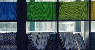 Schwarzes Regal, das voll ist mit Heften in unterschiedlichen Farben - besser durchs Studium kommen mit einem MS Surface.