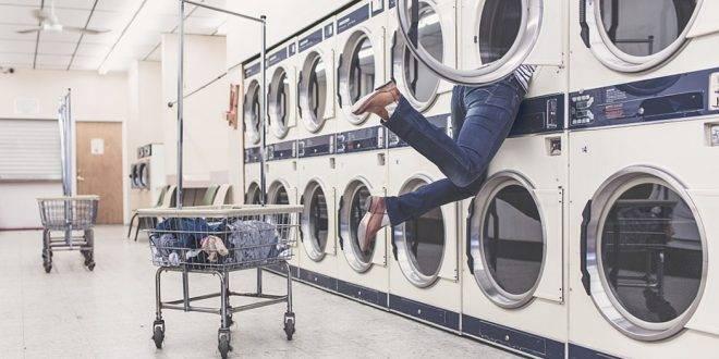 Aneinander gereihte aufeinander stehende Waschmaschinen, wo eine Frau in einer mit dem Kopf drin steckt und nur ihre Füße zu sehen sind - Dinge, die du machst, wenn du lernen solltest: Hausfrau spielen.