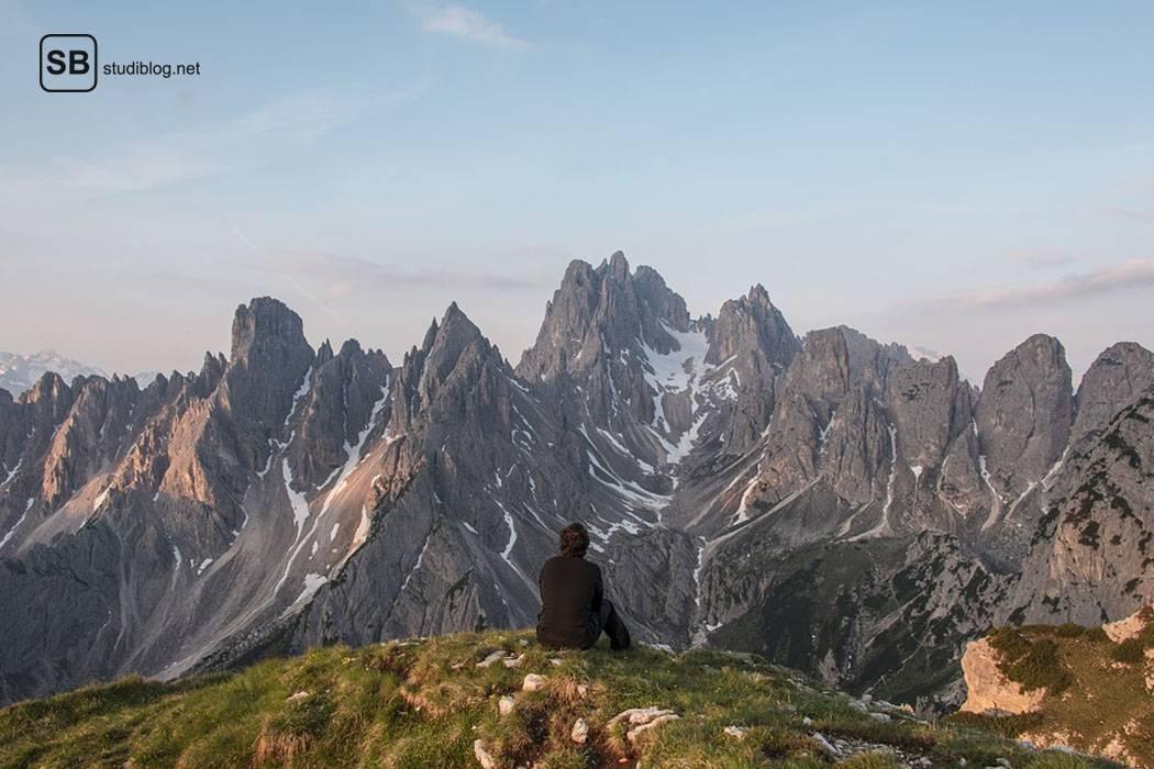 Ein junger Mann sitzt mit dem Rücken zum Fotografen auf einem Felsrand mit Blick ins Gebirge und genießt so seine Pause vom Alltag.