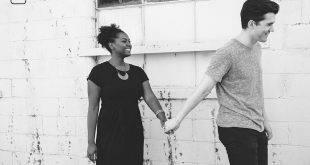 Ein weißer junger Mann hält mit einer dunkelhäutigen jungen Frau während dem Spazierengehen Händchen - rassistische Vagina?