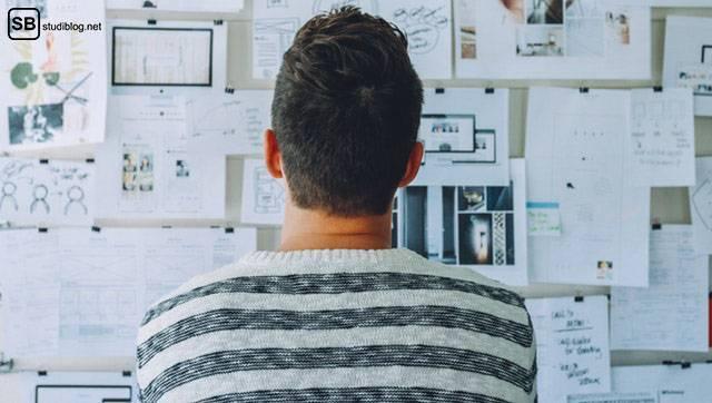 Zeitplan für deine Bachelor- oder Masterarbeit: Thema und Titel finden: Mann steht vor Tafel, an der viele Dokumente hängen