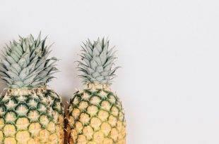Minimalismus: An einer weißen Wand stehen drei Ananas