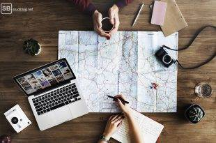 Student's travel guide: A man and a woman are planning their holdiays with a map and a laptop