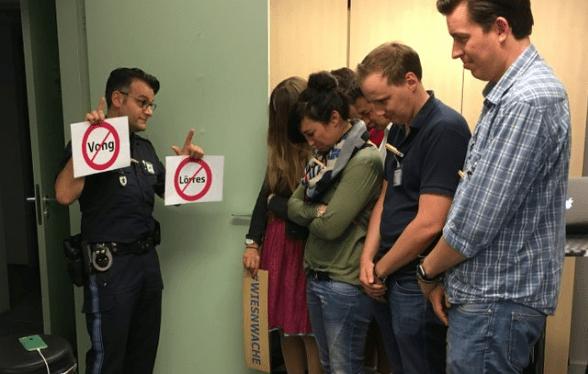 Best of Wiesnwache: Polizist steht mit Schildern, auf denen Lörres und Vong durchgestrichen sind vor 2 Männern und 2 Frauen