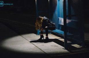 Frau sitzt alleine an einer Bushaltestelle im Spotlight