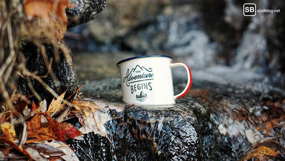 Auslandssemester in Deutschland: Tasse mit der Aufschrift The Adventure begins steht im Wald