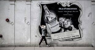 Studiengang Marketing: Frau läuft an einer Street-Art-Werbung für Whisky vorbei