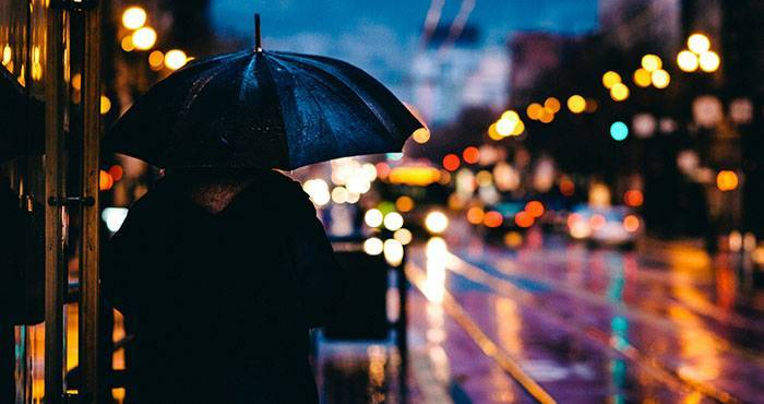 Nostalgie: Person ist alleine bei Regen mit einem Regenschirm in der nächtlichen Stadt unterwegs