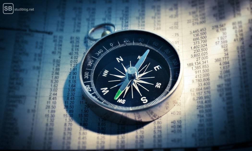 Studiengang-Wahl Wirtschaft: Ein Kompass liegt auf einem Blatt Papier mit tabellarisch eingetragenen Zahlen