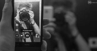 Eure Spiegelselfies machen mir Angst! Junge, der sich in einem Spiegel, in einem Smartphone mit einer Spiegelreflexkamera fotografiert