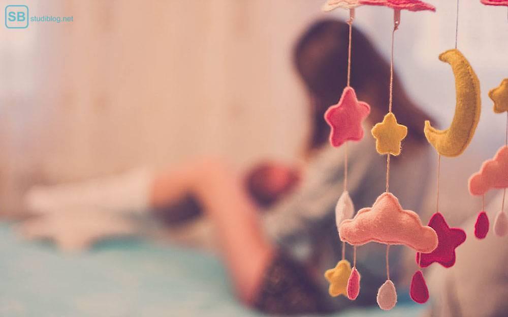 Studieren mit Kind: Im Vordergrund ist ein Traumspiel zu sehen, im Hintergrund eine junge Frau, die mit ihrem Kind im Arm auf dem Bett liegt