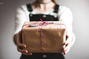 Geschenktipps für Weihnachten für Studenten: Studentin hält ein Päckchen mit Zuckerstangen in die Kamera