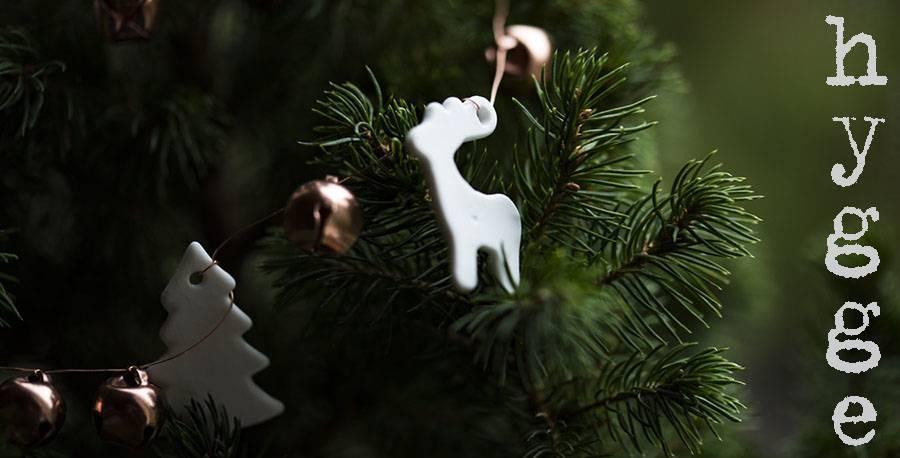Hygge in der Weihnachtszeit: Tannenzweig mit Glöckchen, Rentier und Tannenbaum