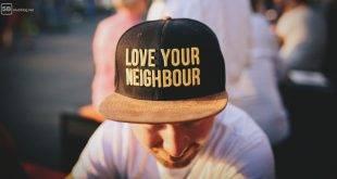 """Meine Nachbarin, die Bitch! Mann, der eine Mütze mit der Aufschrift """"Love your Neighbour"""" trägt"""