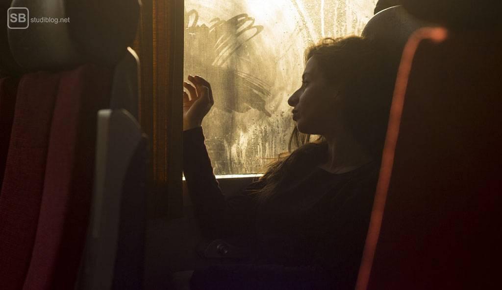 Langeweile nutzten: Frau sitzt in einem Bus, schaut aus dem Fenster und langweilt sich