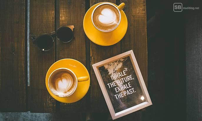 Veränderung - Kaffeetisch, auf dem zwei Tassen stehen und ein Schild mit der Aufschrift: Inhale the Future, Exhale the Past
