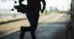 Schemenhaft erkennbarer Mensch läuft mit einem Longboard in der Hand am Bahnsteig entlang - Zu spät mit dem Lernen angefangen.