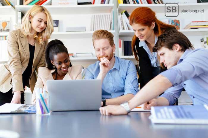 Studentengruppe steht um Notebook herum, auf der Suche nach dem Traumjob