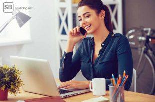 Gut gelaunte Frau am Schreibtisch vor einem Laptop mit einem Handy in der Hand zum Thema - Online Bewerbung, wie bewerbe ich mich richtig