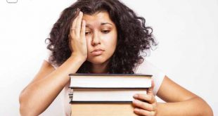 Aufschieberitis, Studentin sitzt über Büchern und ist verzweifelt