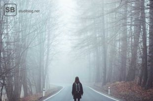 Studentein steht auf einer einsamen Straße zwischen Bäumen zum Thema Versagensangst