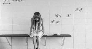Studentin sitzt auf Bank und hat eine Strichliste ihrer Sorgen an die Wand gemalt