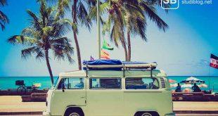 Ein VW-Bulli T1 vor einem Palmenstrand zum Thema Billigurlaub für Studenten, so gelingts