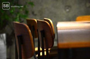 Holztisch mit vier leeren Holzstühlen drum herum - Ärztemangel.