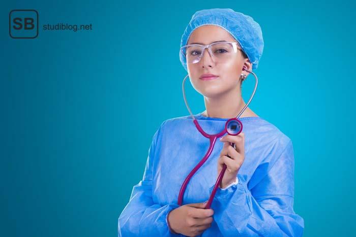 Studentin der Allgemeinmedizin in OP-Gewand, mit Schutzbrille, Haarnetz und pinkem Stethoskop blickt in die Kamera.