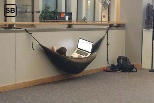 In der Bibliothek liegt ein Student in der Hängematte und liest etwas am Laptop - Dinge, die arme Studenten machen.