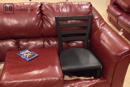 """Auf einer roten Couch wurde ein Sitzplatz durch einen schwarzen Holzstuhl """"repariert"""" - Dinge, die arme Studenten machen."""