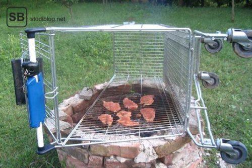 Einkaufswagen liegt über einer Feuerstelle und wird als Grillrost verwendet auf dem Fleischstücke liegen - Dinge, die arme Studenten machen.