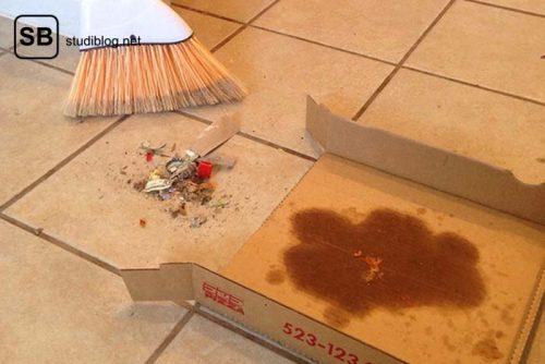 Ein benutzter Pizzakarton wird als Kehrschaufel verwendet - Dinge, die arme Studenten machen.