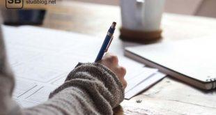 Frau in braunem Häkelpulli macht sich mit blauem Kugelschreiber und einer Tasse Kaffee Notizen zu ihrer Doktorarbeit.