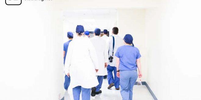 Sieben Ärzte in weißen Kitteln und blauen Hosen gehen weg in einem Gang mit weißen Wänden - Famulatur, Praktikum klinischer Teil des Medizinstudiums.