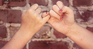 """Zwei Hände geben sich den """"kleinen Finger-Schwur"""" vor einer Backsteinwand - Hippokratischer Eid."""
