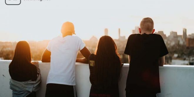 Die Jugend - vier Jugendliche, zwei Jungs und zwei Mädchen, sehen dem Sonnenuntergang an einem Balkon stehend entgegen.