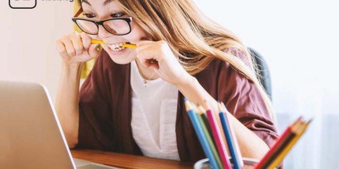 Studentin sitzt vorm Laptop, beißt auf einen Bleistift und und bestimmt angestrengt ihren Lerntyp.