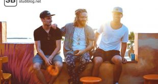Drei Männer sitzen nebeneinander im Sonnenuntergang auf einer Mauer und lachen - Die Entwicklung des Geschmacks in Sachen Mann.