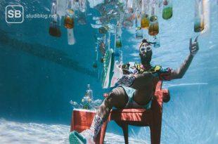 Mann mit dunkler Hautfarbe auf einem roten Stuhl am Poolgrund mit unzähligen Flaschen an der Wasseroberfläche - Medizinerparty