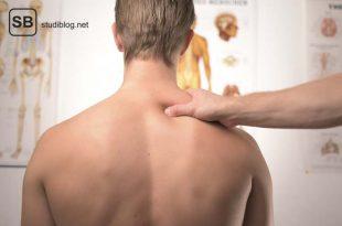 Einem jungen Mann wird die Schulter massiert als manuelles Verfahren zur Heilung - Osteopathie.