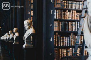 Schwarze Bücherregale mit alten Büchern, vor denen je eine Büste steht - Quellen für eine Studienarbeit.