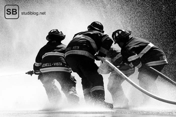 Schwarz-Weiß: Vier Männer der Feuerwehr löschen mit zwei Schläuchen ein Feuer - Als Nebenjob im Studium zum Rettungsdienst.