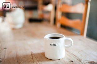 Eine weiße Kaffeetasse mit dem Aufdruck 'Begin' steht auf einem Holztisch - Start Praktisches Jahr im Medizinstudium.