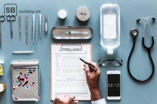 Männerhande arbeiten an dem täglichen Bericht mit Stethoskop, Skalpellen, Scheren, Spritzen und Tabletten geordnet um das Klemmbrett rum am Schreibtisch liegend.