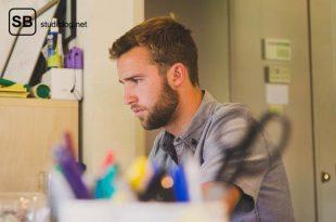 Männlicher Student sitzt am Schreibtisch und lernt für den TMS (Test für medizinische Studiengänge).